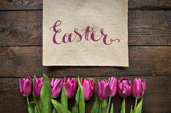 Pink, tulips bunch on dark barn wood planks background. Happy Easter brush nib lettering calligraphy. Pink, tulips bunch on dark barn wood planks background stock photography