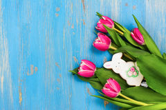 Pink tulips and bunny cookie on blue background Stock Image