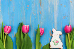 Pink tulips and bunny cookie on blue background Stock Photo