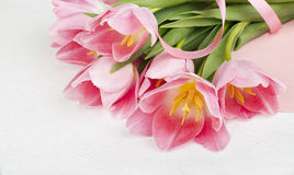Pink tulips with a card on a white wooden background Royalty Free Stock Photography