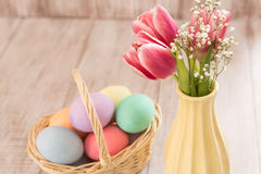 Pink Tulips and Colorful Easter Eggs. Pink tulips in a vase with a basket of colorful Easter eggs Stock Photos