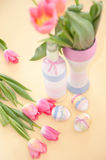 Pink tulips, Easter eggs and yarn wrapped bottle Stock Photo