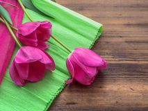 Pink tulips, floral arrangement on wooden background with green paper and space for message. Background for Mother`s Day. 8 March and other greeting cards or stock photography