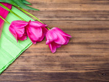 Pink tulips, floral arrangement on wooden background with green paper and space for message. Background for Mother`s Day. 8 March and other greeting cards or stock photos