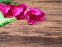 Pink tulips, floral arrangement on wooden background with green paper and space for message. Background for Mother`s Day Stock Photography