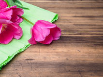Pink tulips, floral arrangement on wooden background with green paper and space for message. Background for Mother`s Day. 8 March and other greeting cards or royalty free stock photos