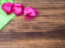 Pink tulips, floral arrangement on wooden background with green paper and space for message. Background for Mother`s Day. 8 March and other greeting cards or stock photo