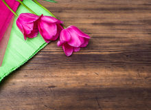 Pink tulips, floral arrangement on wooden background with green paper and space for message. Background for Mother`s Day. 8 March and other greeting cards or royalty free stock photography
