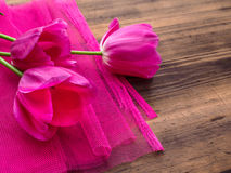 Pink tulips, floral arrangement on wooden background with pink mesh and space for message. Background for Mother`s Day Royalty Free Stock Image
