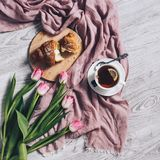 Pink tulips flowers and croissant for breakfast royalty free stock images