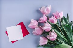 Pink tulips flowers and sheet of paper over light blue background. Greeting card or wedding invitation. Flat lay, top view, copy space royalty free stock photos