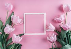 Pink tulips flowers and sheet of paper over light pink background. Saint Valentines Day frame or background.