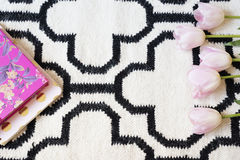 Pink Tulips frame over Scandinavian rug. White black pattern. Lifestyle concept. Copy Space. Flower Frame, Border Stock Photos