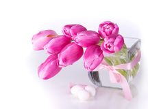 Pink tulips  in glass vase with eggs  . Pink tulips in glass vase with eggs on white background Royalty Free Stock Images