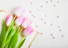 Pink tulips with heart and beads over white wooden table. Closeu Royalty Free Stock Photography