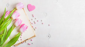 Pink tulips with heart and beads over white wooden table Stock Photo