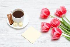 Pink tulips, mug of coffee and cinamon, light wooden background. Pink tulips, mug of coffee and cinamon, light wooden background Stock Photos