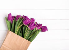 Pink tulips in a paper bag on the white wooden table. Top view Royalty Free Stock Image