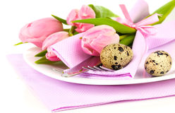 Pink tulips with quail eggs in a plate. On a white background. romantic still life with fresh flowers Stock Image