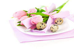 Pink tulips with quail eggs in a plate. On a white background. romantic still life with fresh flowers Royalty Free Stock Photography