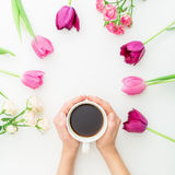 Pink tulips, roses and black coffee on white background. Flat lay. Top view. Valentines Day background. Royalty Free Stock Photo