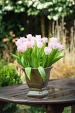 Pink tulips on a wet garden table Royalty Free Stock Photos