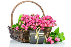 Pink tulips and in the wicker and a gift Royalty Free Stock Photography
