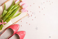 Pink tulips with women`s shoes over white wooden table. Spring c Stock Photo