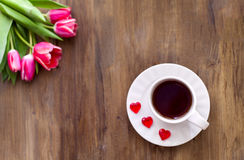 Pink tulips on wooden background, two cups of tea and coffee on saucers with hearts marmalade Royalty Free Stock Images