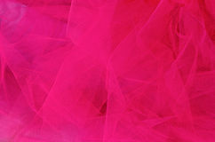 Pink Tulle. Background of bright fuchsia tulle fabric for girl's tutu or veil Stock Photos