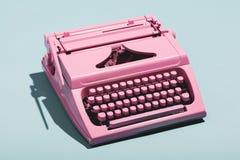 Pink typewriter on a blue pastel background. Vintage machine. Journalism Stock Images