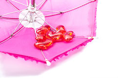 Pink umbrella with romantic red hearts Stock Image
