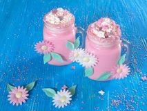 Pink unicorn milk shake with whipped cream, sugar and sprinkles. Set on a blue wooden board Stock Photos