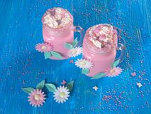 Pink unicorn milk shake with whipped cream, sugar and sprinkles. Set on a blue wooden board Stock Images