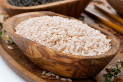 Pink unpolished rice in a wooden bowl, close-up Stock Image