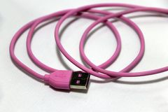 Pink used USB plug with cable on the white background. royalty free stock photos