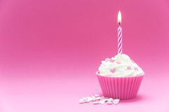 Pink valentine cupcake. Pink cupcake with burning candle and pink background Royalty Free Stock Photo