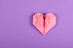 Pink Valentine origami on a lilac background. Heart of paper. Royalty Free Stock Images