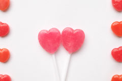 Pink Valentine`s day heart shape lollipop small red candy in cute pattern on empty white paper background. love concept. top view. Stock Photos