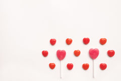Pink Valentine`s day heart shape lollipop small red candy in cute pattern on empty white paper background. love concept. top view. Stock Photo