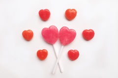 Pink Valentine`s day heart shape lollipop small red candy in cute pattern on empty white paper background. love concept. top view. Royalty Free Stock Photography