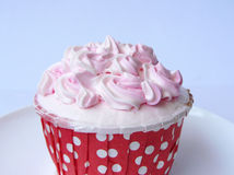 Pink Vanilla cupcake. Vanilla cake in paper cup decorated with white and pink creamy, close up side view on a white plate.  on white background Royalty Free Stock Photos