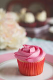 Pink vanilla rose cupcake on plate with text space Royalty Free Stock Photo