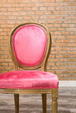 Pink velvet classic style chair. With old brick wall background Stock Photo