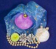 Pink velvety New Year`s ball , the burning candle and a pearl beads on a blue background - New Year`s composition, a card.  Royalty Free Stock Photo