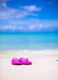 Pink vibrant beach flip flops on white sand on sea Stock Photos