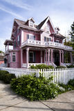 Pink Victorian house. Beautiful pink Victorian haunted house with porch and balcony surrounded by a white picked fence Royalty Free Stock Photo