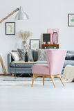 Pink vintage armchair in room. Pink vintage armchair near coffee table with black vase in living room with grey settee and lamp Royalty Free Stock Images