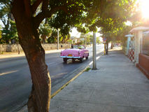 Pink vintage car on the road Royalty Free Stock Photography