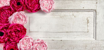 Pink vintage flowers on aged door Stock Photo